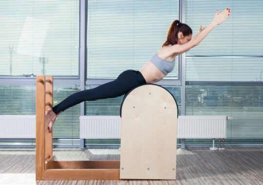 47935424 - pilates, fitness, sport, training and people concept - smiling woman doing  exercises on ladder barrel.